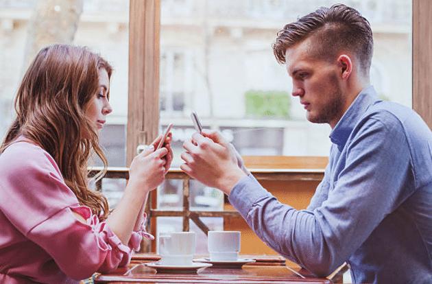 ennui couple smartphones restaurant
