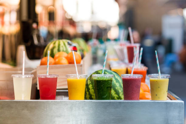 Close up color image depicting freshly made fruit juices and smoothies on display in a row and for sale at a food and drink market in London, UK. Selective focus on the plastic cups containing the fresh smoothies. In the background people are blurred out of focus. Room for copy space.