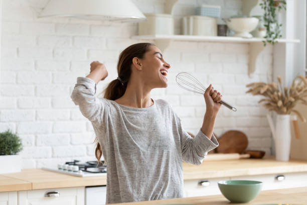 Excited funny girl singing into whisk, having fun in modern kitchen at home, happy girl holding beater as microphone, dancing, listening to music, having fun with kitchenware, preparing breakfast
