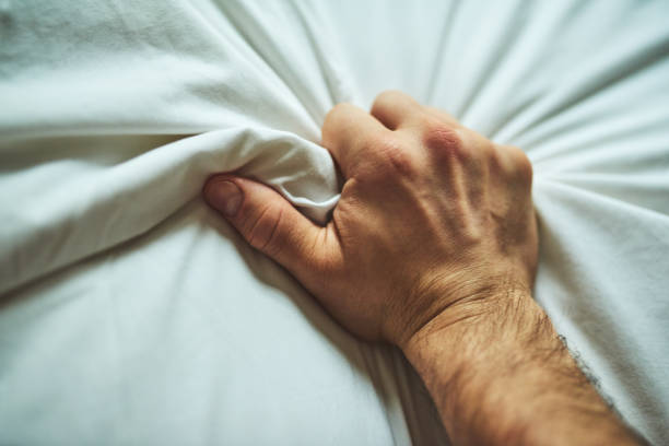 Closeup shot of an unrecognizable man's hand grabbing a sheet in pleasure