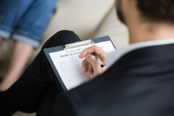 Close up of male psychologist or doctor holding clipboard with medical card listening to patient problems, expert or counselor take notes or fill information during therapy session or counseling