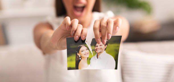 Divorce Concept. Unrecognizable Furious Girl Tearing Apart Photo Of Happy Couple Indoor. Selective Focus, Panorama, Cropped
