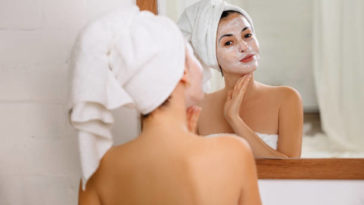 Woman with towel is applying mask on her face in front of the mirror at home. Skin care.