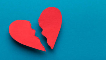 Sign of divorce. Broken paper heart on blue background, top view, copy space