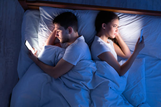 Spouses Using Smartphones Texting With Lovers Lying