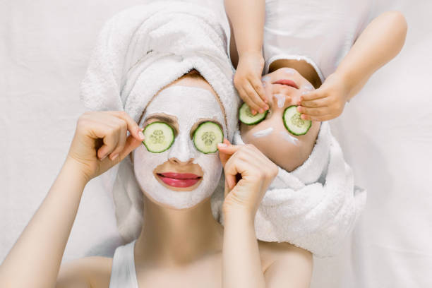 Mom and her 2 years old baby girl having fun together, making clay facial mask and cucumber slices on eyes. Mother with child doing beauty treatment together. Family time, spa and beauty, mothers day.