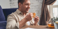 Smiling man with his eyes closed enjoying the aroma of the freshly brewed chamomile tea