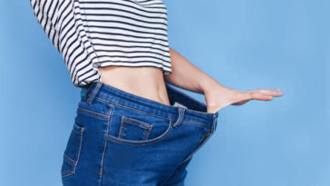 Slim woman body lose weight and show tobig jeans.