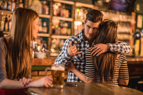 Unfaithful young man in a cafe. He is embracing his girlfriend and making call gesture to another woman behind her back.