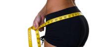 Closeup of a woman measuring her waist