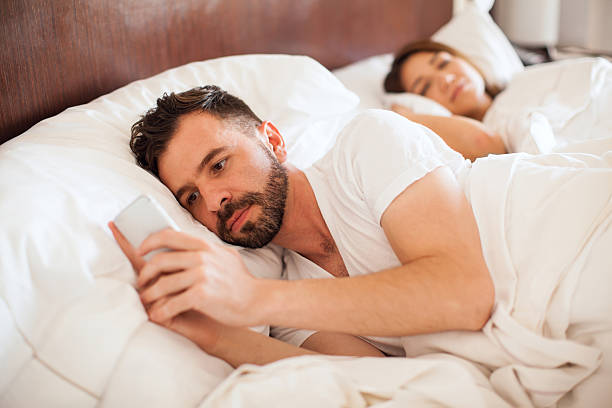 Portrait of a handsome young man with a beard checking his smartphone and texting his lover while his partner sleep