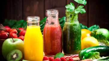 Healthy eating concept: Horizontal shot of three detox drinks in glass bottles with fruits and vegetables all around them on rustic wood table. DSRL studio photo taken with Canon EOS 5D Mk II and Canon EF 70-200mm f/2.8L IS II USM Telephoto Zoom Lens