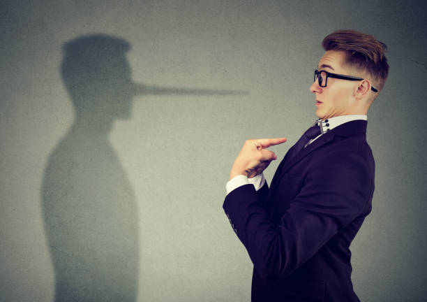Side view of man in suit pointing at himself looking at shadow with long nose of a liar.