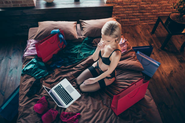 Above high angle view of her she nice-looking stunning adorable, gorgeous attractive lovely feminine lady sitting on bed ordering new clothes collection in loft brick wooden industrial style interior