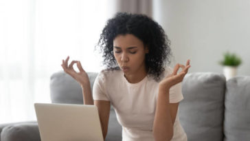 African woman sit on couch near laptop take break reduce stress do yoga meditation exercise to calm down self control get rid of negative emotions, bad e-mail, difficult task, problems at work concept