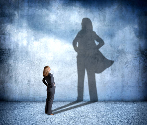 A woman stands with her hands on her hips as she looks up at her shadow that is cast on the wall in front of her that shows her in a confident stance and wearing a cape.