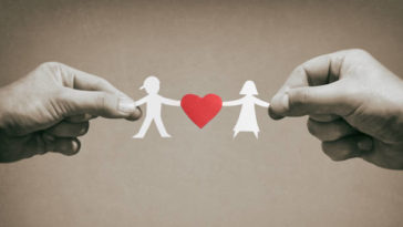 Paper kids with red heart in mom and dad hands.