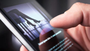 Man looking at a photo of a woman in high heels with mobile phone.