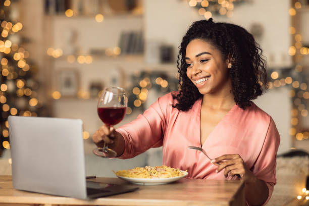 Online Meeting. Happy beautiful black woman making video call with friends or husband during dinner, drinking red wine and toasting, sitting at dining table, eating pasta, celebrating alone at home