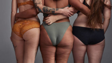 Shot of three young women posing in their underwear against a grey background