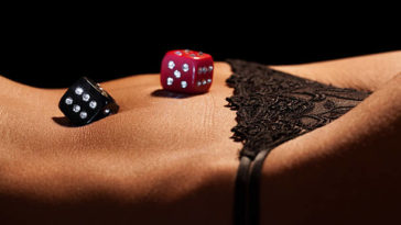 Sexy woman body with dice on the belly