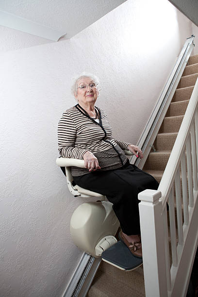 A bright smile from a senior lady using her stair lift to improve mobility and independence