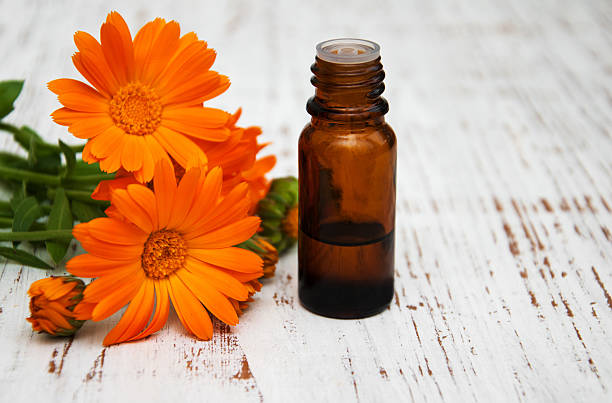 calendula flowers and massage oil on a wooden background