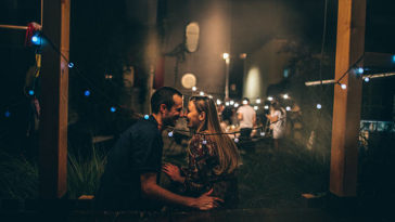 Photo of a lovely couple celebrating love during the dinner party with friends, in an outdoors bistro