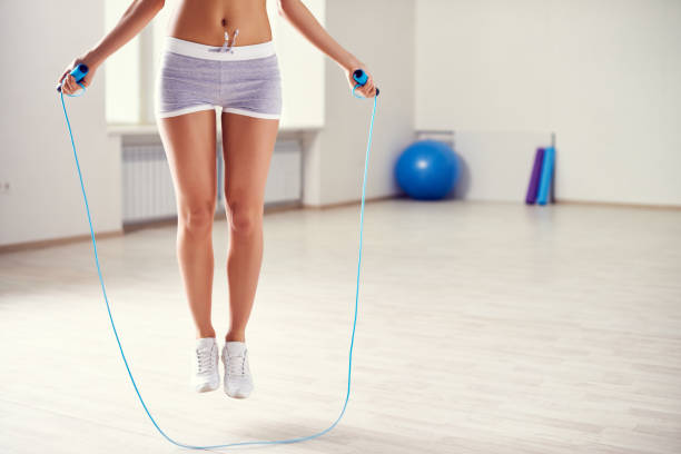 Slim unrecognizable woman jumping through rope in empty fitness gym