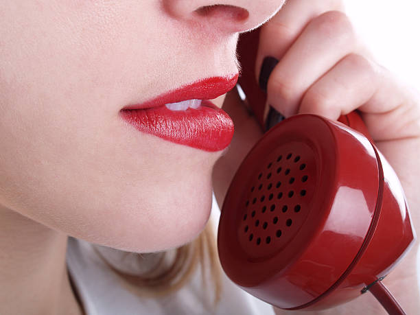 Macro of red phone and woman's mouth; white background
