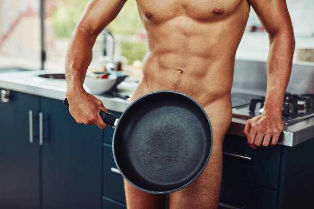Shot of an unrecognizable naked man holding a frying pan in front of his private area in the kitchen at home