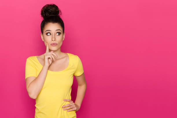 Beautiful young woman in yellow top is holding hand on chin, looking away and thinking. Waist up studio shot on pink background.