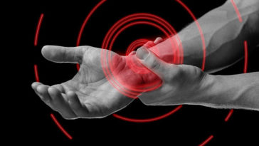 Acute pain in a male wrist. Man holds his hand, black and white image, pain area of red color
