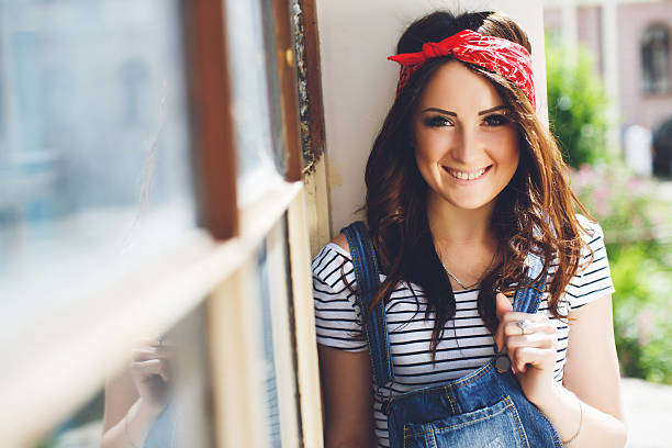 Close up outdoor portrait of happy brunette girl, smiling and looking at camera, wearing bright red bandana and denim overalls. Outdoor sunny day.